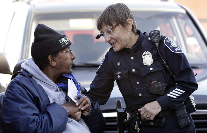In this March 12, 2015, file photo, Seattle police officer Debra Pelich, right, wears a video camera on her eyeglasses as she talks with Alex Legesse before a small community gathering in Seattle.