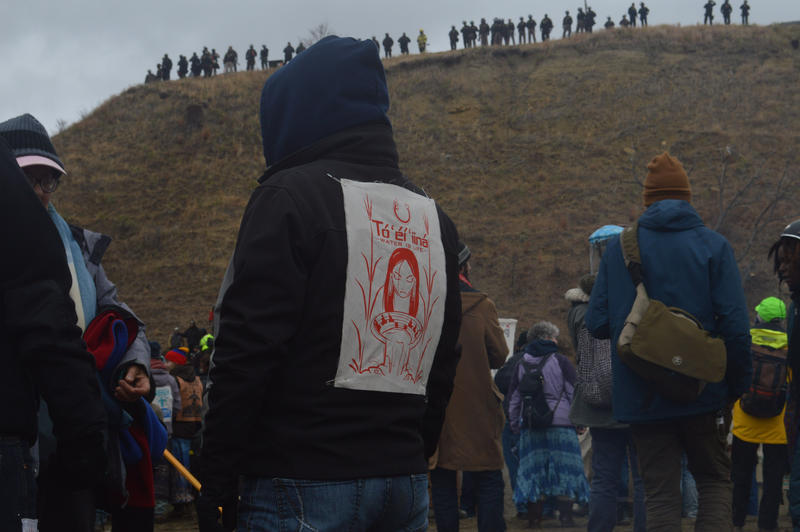"A demonstrator faces police officers at the top of a hill containing Lakota burial sites. His sweatshirt says ""water is life"" in Diné, the Navajo language."