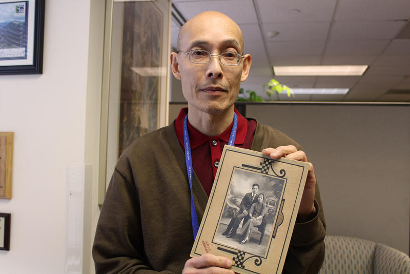 Ron Chew works at the International Community Health Services. He holds a portrait of his parents. His grandfather came to the U.S. illegally during the Chinese Exclusion Act.