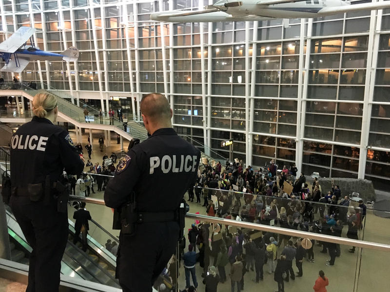 Police look out over a growing protest at Sea-Tac International Airport, where up to 13 people have been detained one day after President Donald Trump issued an executive order banning people from seven Muslim countries.