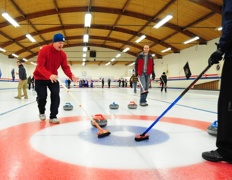 Co-workers move a stone down the ice at Granite Curling Club. The club rents out their facility for group parties.