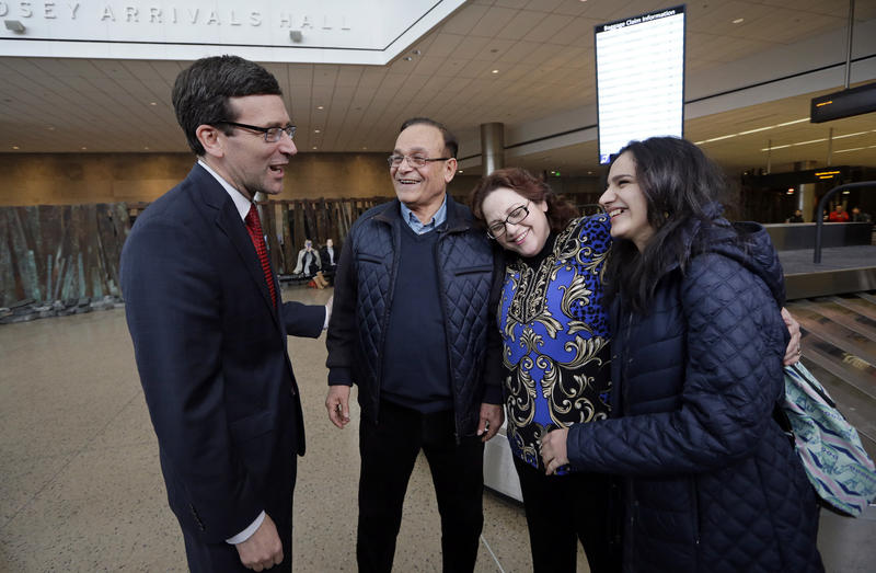 Attorney General Bob Ferguson, left, greets Allen Novak, newly-arrived from Iran, his wife Jayne and their daughter Nikta, Monday, Feb. 6, 2017, at Sea-Tac Airport. Allen Novak joined his family, of Silverdale, Wash., on a conditional resident visa.