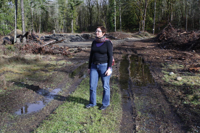 Reporter Carolyn Adolph stands on a development site near Black Diamond, WA. Her fellow reporter Joshua McNichols is behind the camera.
