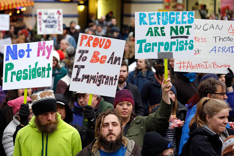 People begin to gather before a rally protesting President Donald Trump's travel ban on refugees and citizens of seven Muslim-majority nations, Sunday, Jan. 29, 2017, in Seattle.