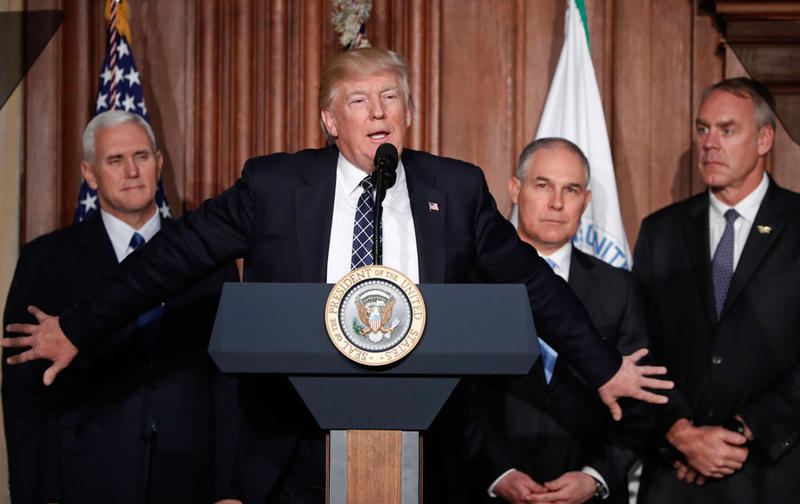 President Donald Trump, accompanied by from left, Vice President Mike Pence, Environmental Protection Agency Administrator Scott Pruitt, and Interior Secretary Ryan Zinke, speaks at EPA headquarters in Washington, March 28.