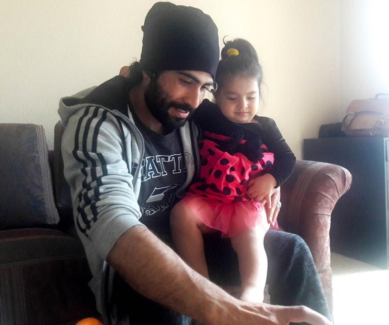 Marwal Frotan plays with his daughter Bushra in their Kent home. Frotan and his family moved to Seattle four months ago.