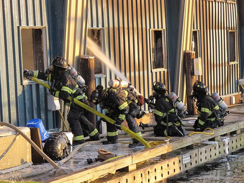 Firefighters put out flames at the Salmon Bay Marina, one of three fires caused by spontaneous combustion this month.