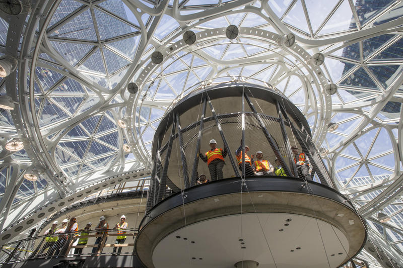 Workers watch the ceremonial first planting in The Spheres at Amazon campus on Thursday.