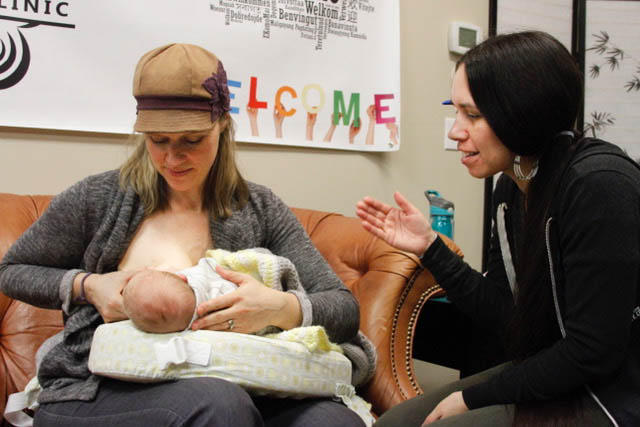 Lactation consultant Camie Goldhammer helps 5-week-old Darius latch onto his mother, Carole Gibson-Smith. Goldhammer, a social worker by training, focuses on breastfeeding in communities of color, particularly in Native communities.