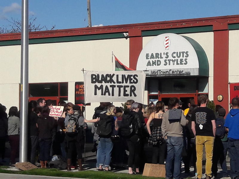 People hold a Black Lives Matter sign at a demonstration against gentrification in Seattle's Central District