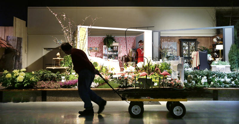 "A worker pulls a wagon past a ""his and hers"" garden theme set at the Northwest Flower & Garden Show Tuesday, Feb. 19, 2013, in Seattle."