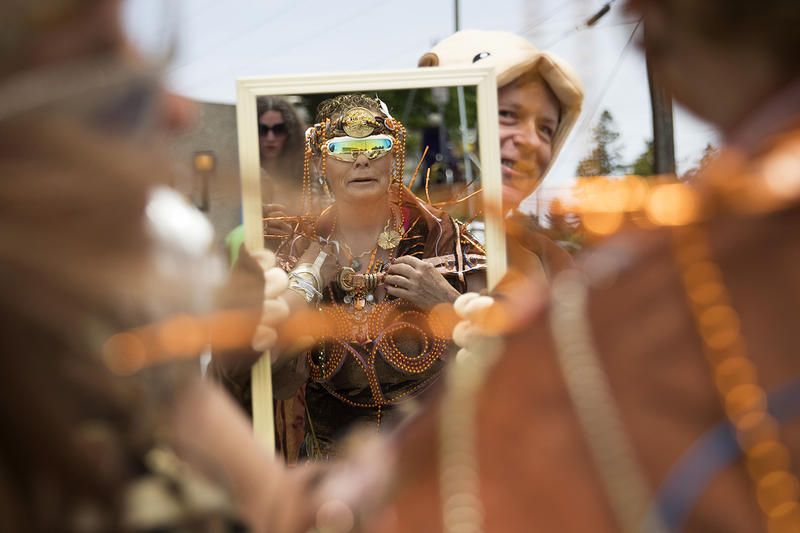 Shannon Nowell examines her reflection as Ken Hartford holds a mirror for her, before the start of the Fremont Solstice Parade.