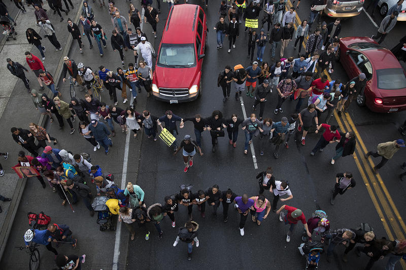 People link arms as they walk toward a police blockade at the intersection of NE Pacific St. and Montlake Blvd. NE after a vigil for Charleena Lyles on Tuesday, June 19, 2017, in Seattle, Washington.