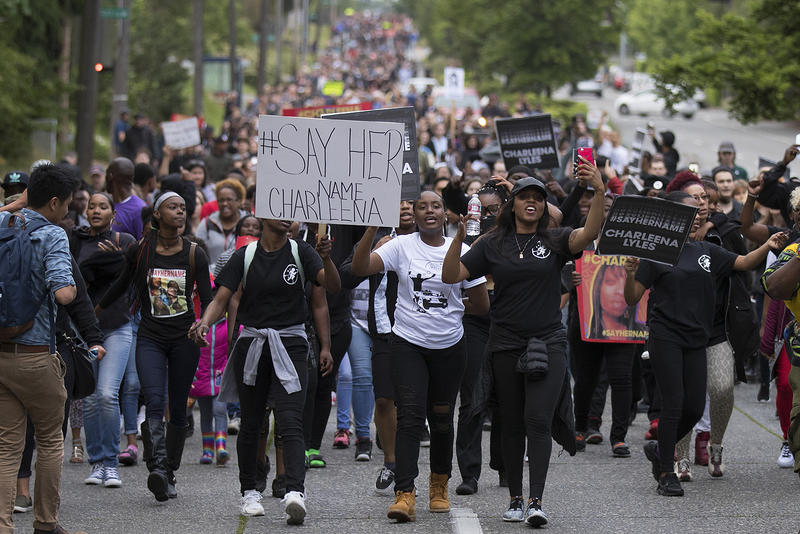A large crowd walks on Sand Point Way NE on Tuesday, June 19, 2017, after a vigil honoring Charleena Lyles at the Solid Ground Brettler Family Place, in Seattle, Washington.