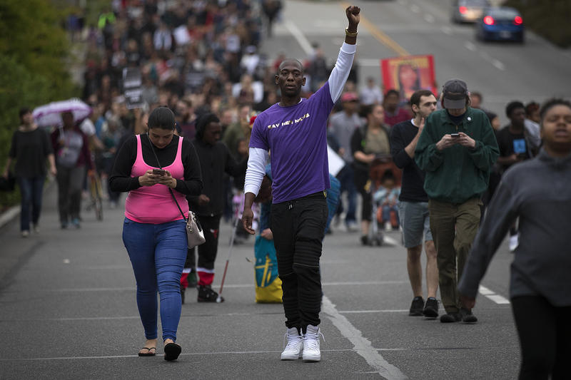 Bruce McGregor raises his fist in the air while walking with a large crowd after a vigil honoring Charleena Lyles on Tuesday, June 19, 2017, in Seattle, Washington.