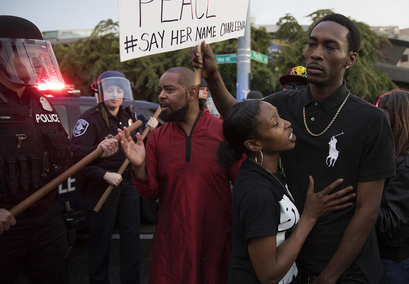 Andre Taylor, Shanee Isabell, center, and Chris Cressel, right, stand next to a line of Seattle Police Officers that are blocking the intersection of NE Pacific St., and Montlake Blvd. NE., on Tuesday, June 19, 2017, in Seattle, Washington.