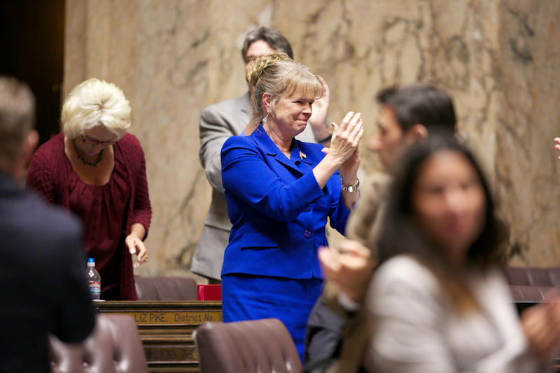 Washington state Rep. Judy Warnick applauds after the capital budget is adopted as the last bill of the 2013 session