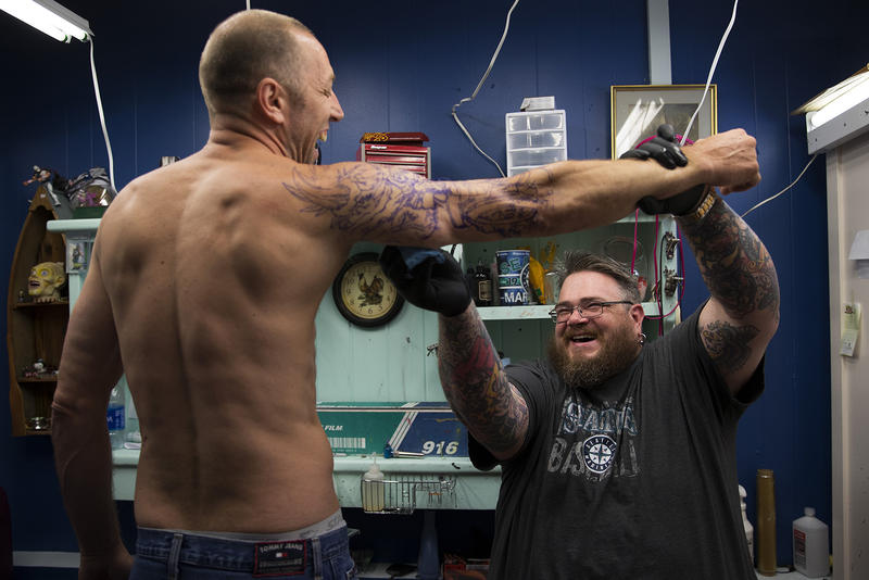 Mike Heath, left, laughs  as Blue Collar Tattoo owner Sean Ewan cleans his arm before tattooing a tribute to Metallica, on Wednesday, July 5, 2017, in Bremerton, Washington.