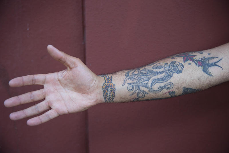 Aviation rescue swimmer Sakri Kmimech, 22, shows off his tattoos on Thursday, June 29, 2017, in Bremerton, Washington. 'That's the sailors score knot, it symbolizes unity,' he said about the tattoo on his wrist.