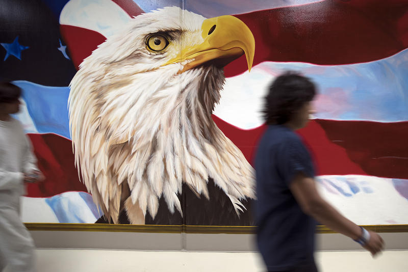 Dozens of murals hang on the walls at the Northwest Detention Center. They're painted by detainees, and the designs must be approved by staff. Painting is also considered a voluntary job, and the artists are paid $1 per day for their work.