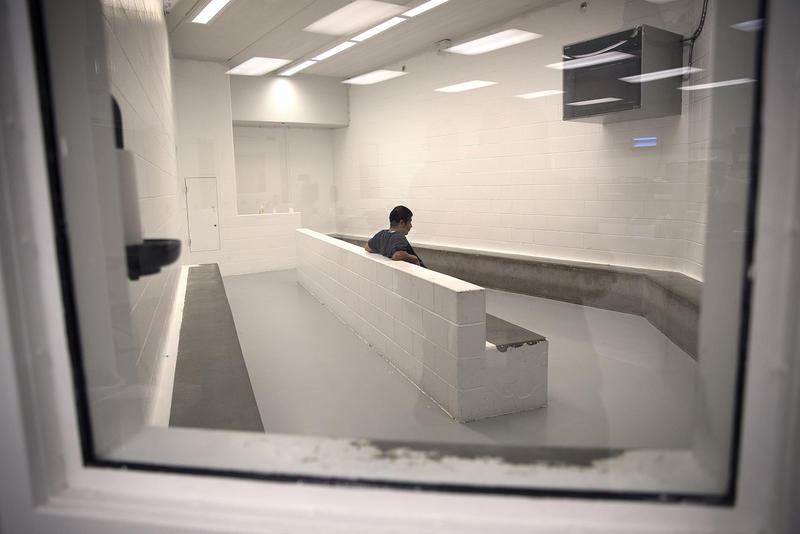 A detainee sits in the intake area at the Tacoma Detention Center in 2017.