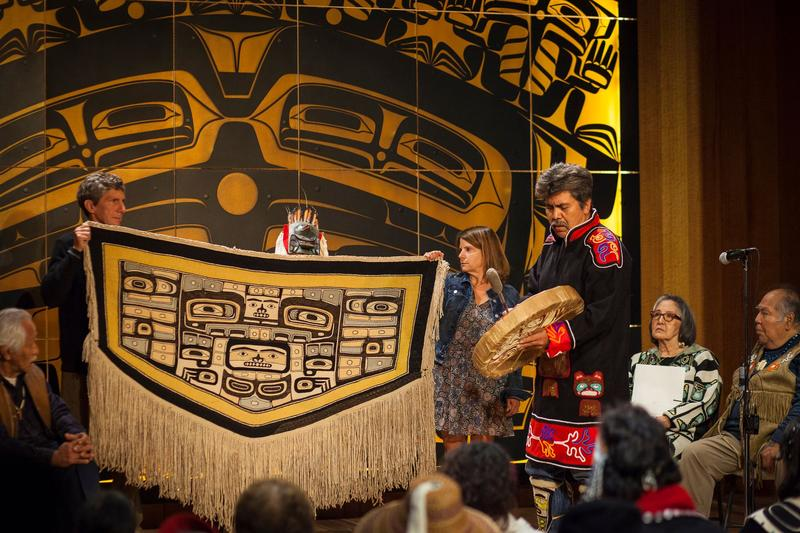Bruce and Gretchen Jacobsen hold the Chilkat robe they donated to the Sealaska Heritage Institute as Joe Zuboff, Deisheetaan, sings and drums and Brian Katzeek (behind robe) dances during the robe's homecoming ceremony Saturday, August 26, 2017.