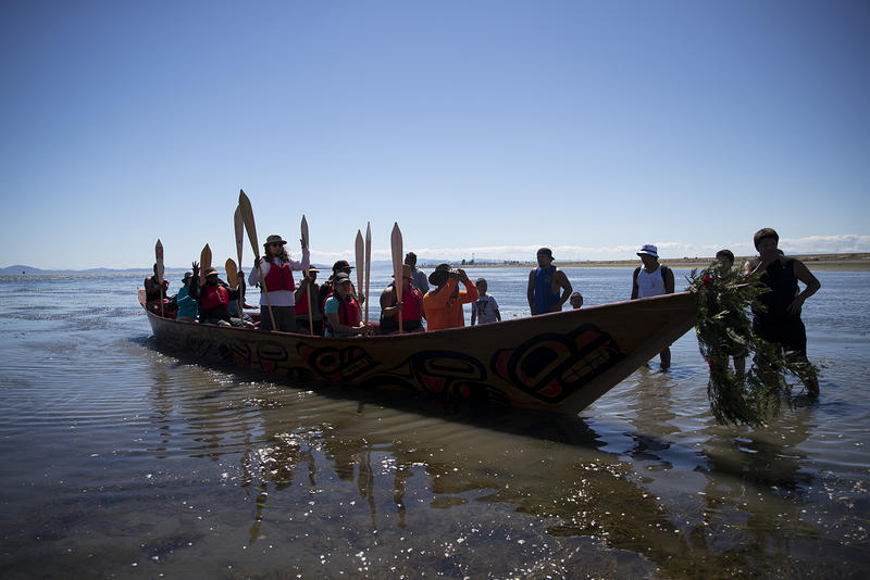 Members of the 'Emma canoe' arrive on the shore of the Tsawwassen Indian Reserve after the first leg of their multi-day canoe journey on Thursday, July 27, 2017, in Tsawwassen, British Columbia.