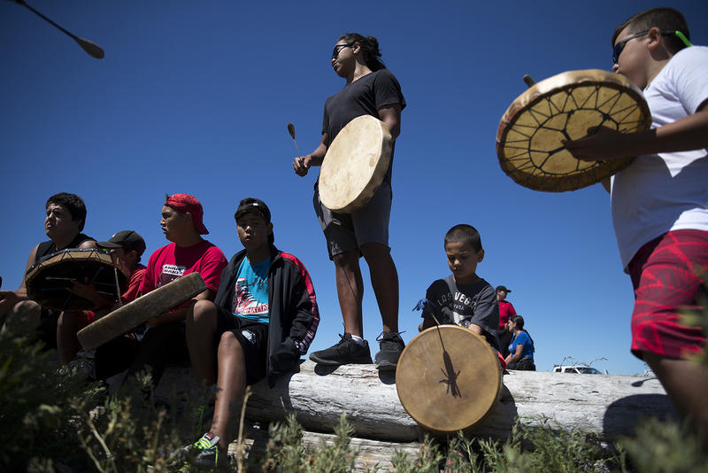 Shxwhá:y drummer Leonard Gladstone, 17, center, stands while drumming on Thursday, July 27, 2017, while waiting for the 'Emma canoe' to arrive in Tsawassen, British Columbia.
