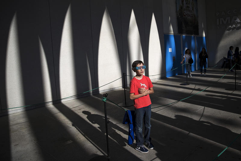 Rafaelle Del Pesce, 9, looks toward the sun during the solar eclipse on Monday, August 21, 2017, at the Pacific Science Center on 2nd Ave., in Seattle.