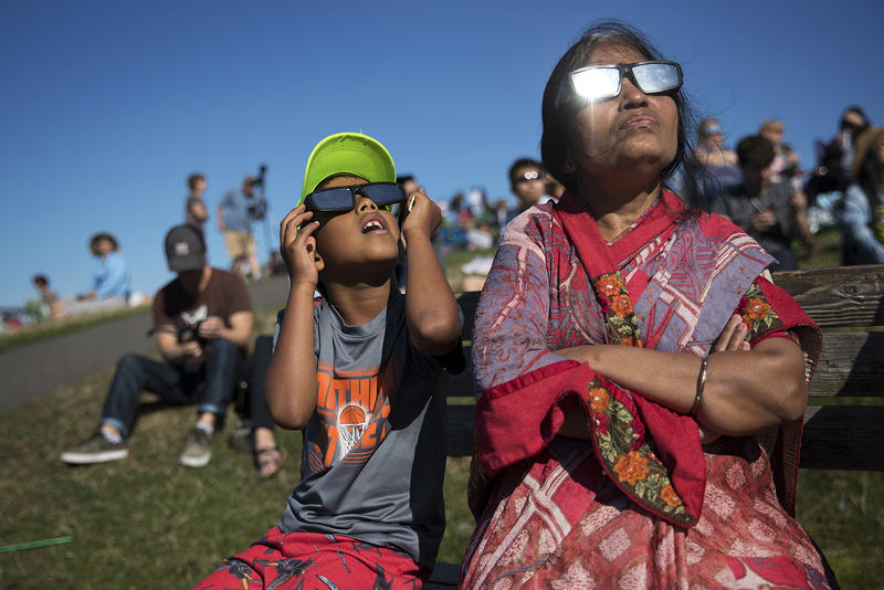 Ayush Jakhotia, 7, left, watches the solar eclipse with his grandmother, Radha Jakhotia, right, on Monday, August 21, 2017, from Gas Works Park, in Seattle. KUOW Photo/Megan Farmer