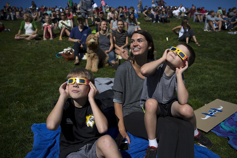 From left, Wyatt Godwin-Austen, 10, Megan Cordell, and Hunter Godwin-Austen, 8, watch the solar eclipse from Gas Works Park on Monday, August 21, 2017, in Seattle. KUOW Photo/Megan Farmer