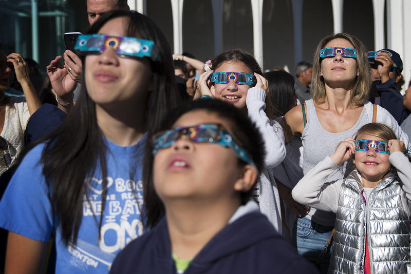 From left, Helen Le, Cadin Le, 10, Anastasia Wilcox, 12, Lesia Wilcox, and Anna Wilcox, 7, look toward the sun during the solar eclipse on Monday, August 21, 2017, at the Pacific Science Center in Seattle. KUOW Photo/Megan Farmer