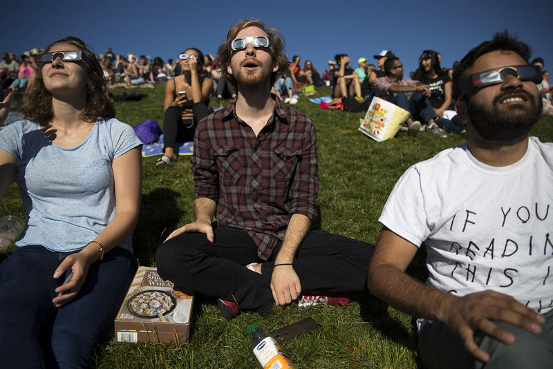 From left, Emily Bram, Trent McCormick and Abhi Kelkar watch the solar eclipse on Monday, August 21, 2017, from Gas Works Park in Seattle.