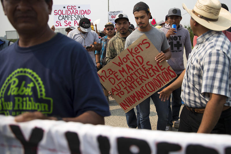 Dionicio Hernandez Rivera, 21, center, marches with other farmworkers on Rock Road toward Sarbanand Farms on Wednesday, August 8, 2017, in Sumas, Washington. H-2A farm workers protested working conditions after Honesto Silva Ibarra died on Sunday.