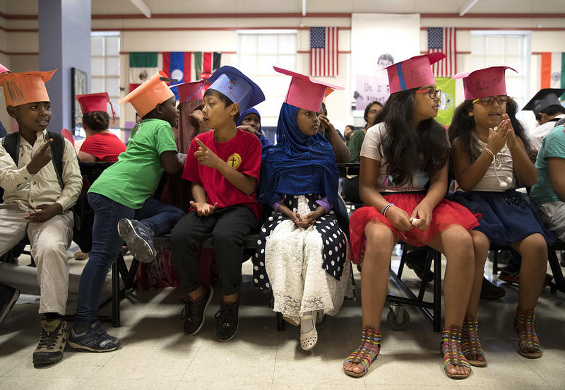 Graduates of the International Rescue Committee summer school program, including Ikran Osman, 5, center, sit in the cafeteria before a graduation ceremony on Thursday, August 3, 2017, at Showalter Middle School in Tukwila.