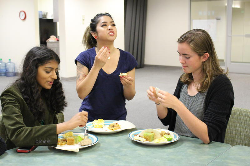 RadioActivians (from left to right) Aliyah Musaliar, April Reyes, and Carlin Bills try some of the potluck dishes.