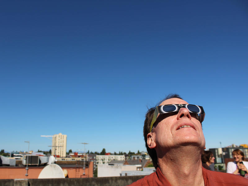 KUOW's Ross Reynolds watches the solar eclipse from the roof of the KUOW parking garage in the University District.