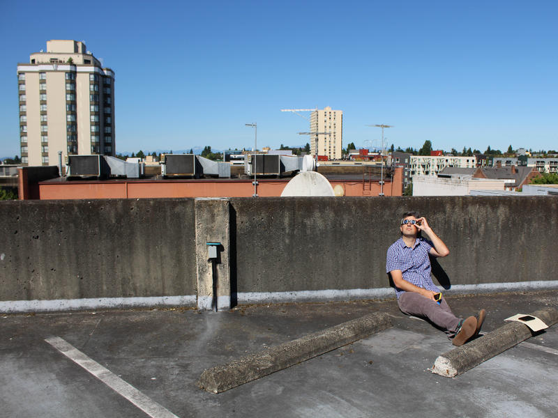 Record producer/editor Jason Pagano watches the eclipse from the roof of the KUOW garage.