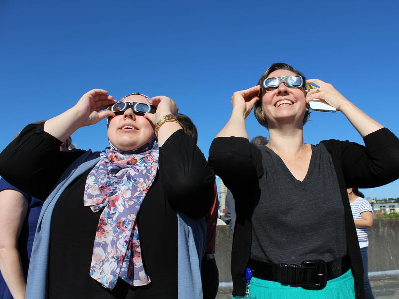 KUOW producer Amina Al-Sadi, left, and editor Jeannie Yandel, look through their eclipse glasses on Monday morning. Amina, who produced many of our eclipse segments, had been looking forward to this moment.