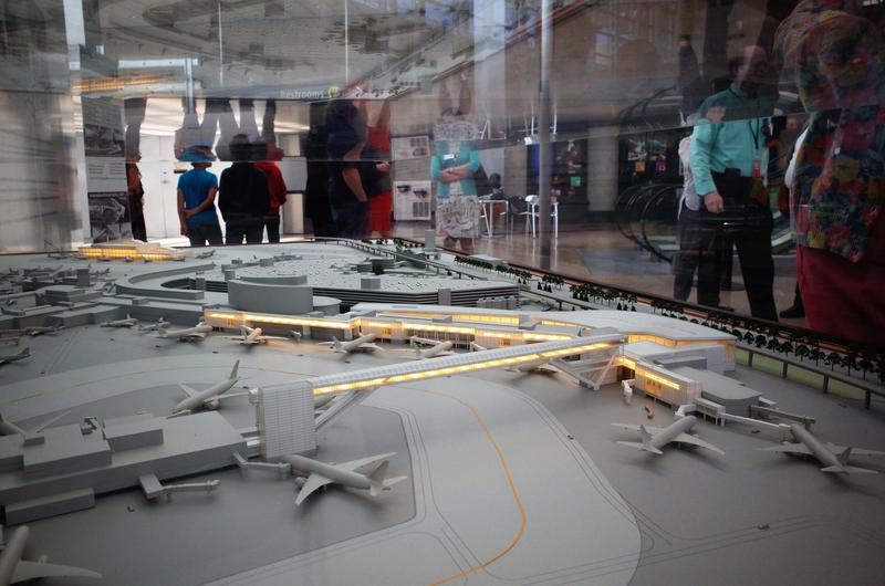 Sea-Tac visitors pass a model of the International Arrivals Terminal, to be completed in 2019.