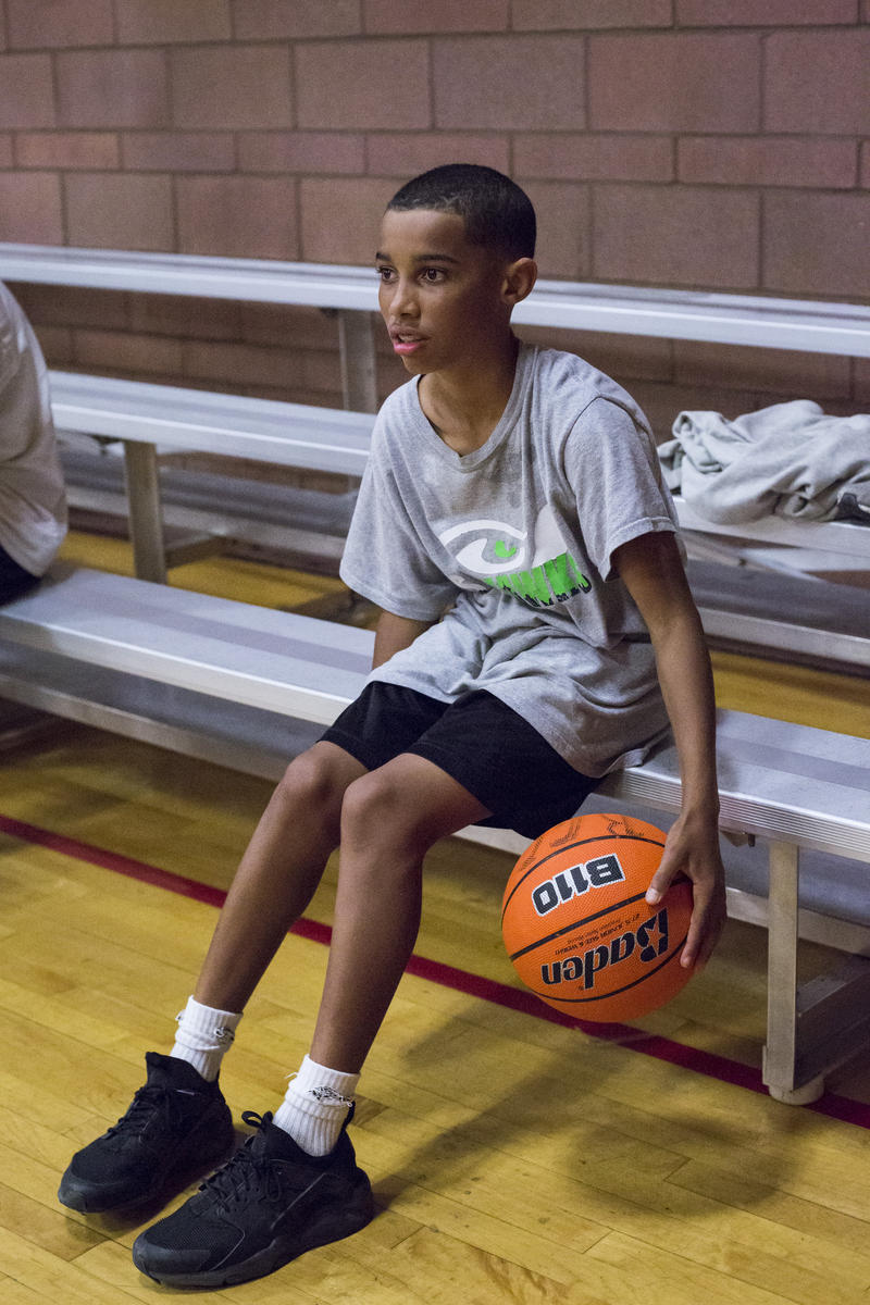 Jamari Jackson watches a basketball game during the Late Night open gym program at the Rainier Community Center on July 21, 2017 in Seattle, Washington. During Late Night, the gymnasium is open until midnight and kids can eat dinner for free as well.