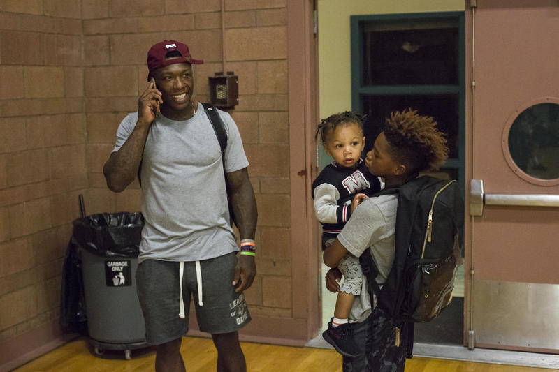 Professional basketball player Nate Robinson, left, who played basketball at the Late Night program when he was young, now brings his son Nyale (right, holding his brother, Nasir) to the program.