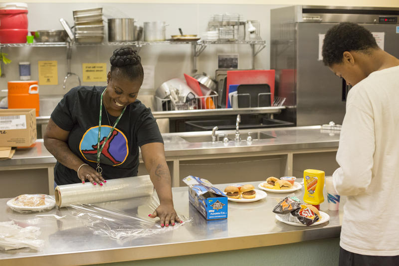 Tanesha Jones, left, prepares free dinner for teens during the Late Night open gym program at the Rainier Community Center on July 21, 2017.