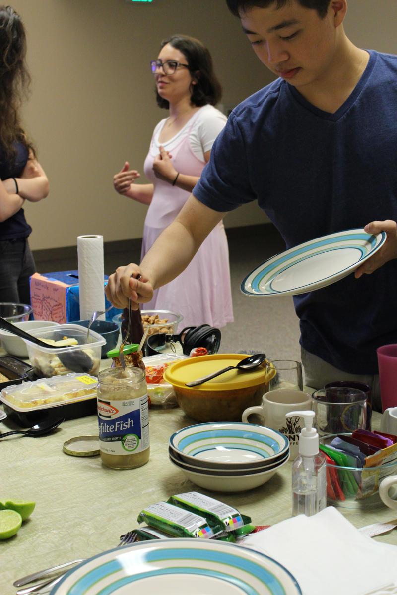 RadioActivian Patrick Liu serves up some gefilte fish, while Noel Gasca awaits her turn.