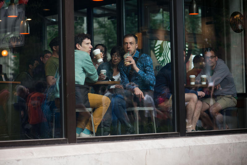 Starbucks patrons watch the anti-fascists march in downtown Seattle, August 13, 2017.