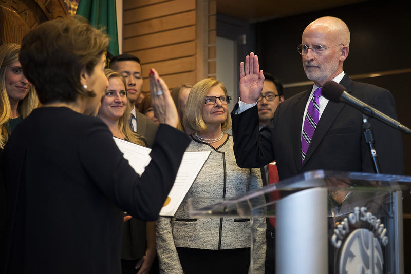 Councilmember Tim Burgess, right, takes the oath of office, administered by Seattle City Clerk Monica Simmons, on Monday, September 18, 2017, becoming the mayor of Seattle, at City Hall in Seattle.
