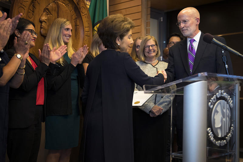 Councilmember Tim Burgess, right, shakes hands with Seattle City Clerk Monica Simmons after taking the oath of office and becoming mayor of Seattle, on Monday, September 18, 2017, at City Hall in Seattle.