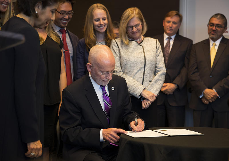 FILE: Then-Councilmember Tim Burgess signs an official document after taking the oath of office and becoming the mayor of Seattle on Monday, September 18, 2017, at City Hall in Seattle.