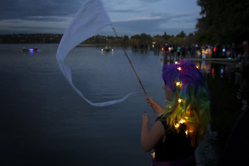 Eliot Wentz, 8, waves a flag in the air before the start of the Luminata lantern parade on Thursday, September 21, 2017, at Green Lake in Seattle.
