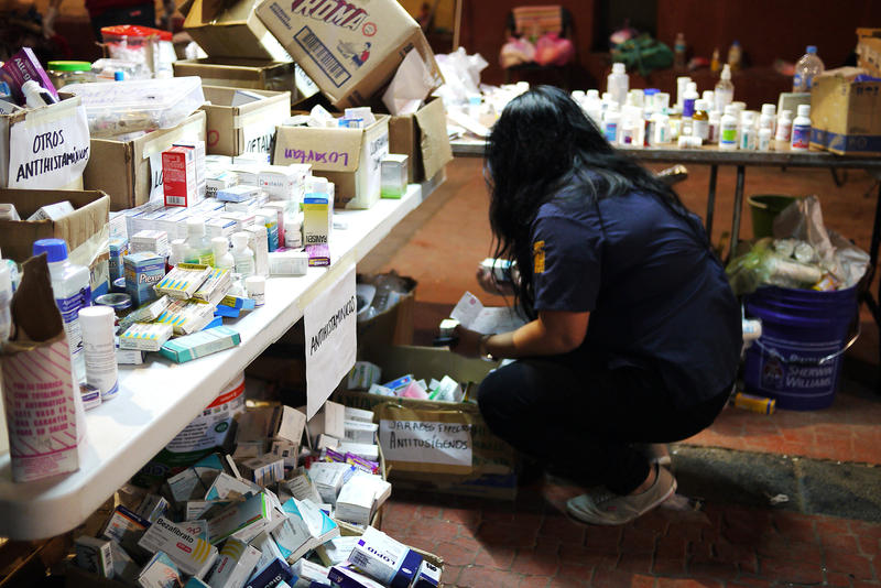 A medical worker sorts through boxes of donations, looking for a specific prescription. Pharmacies in this rural town remained closed while the water was cut off.